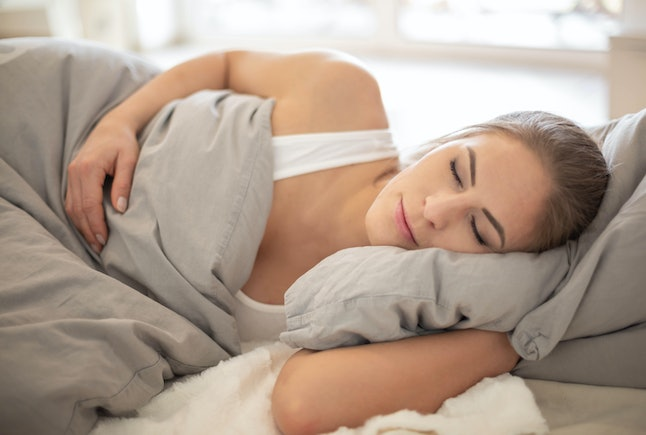 Beautiful blond Woman Sleeping On Bed and is waking up in the mo