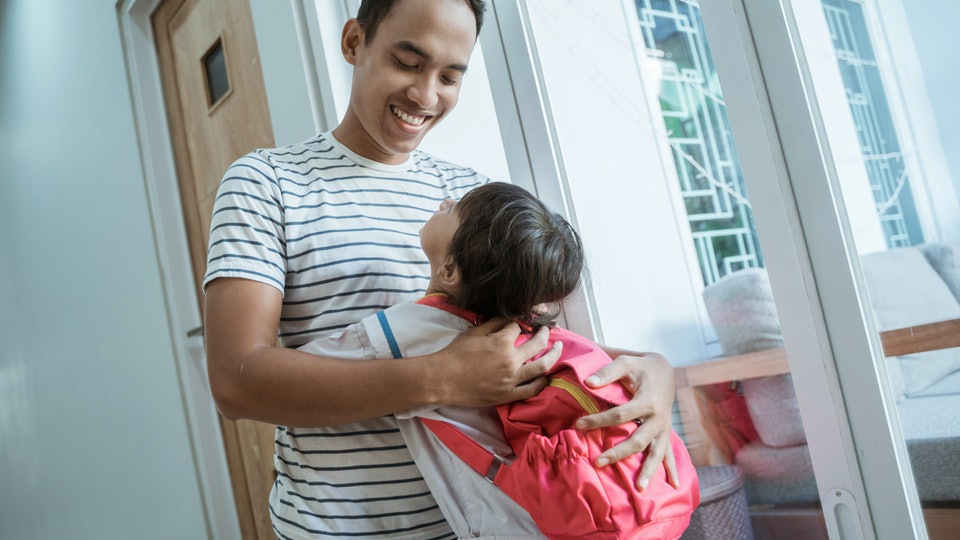 happy asian kindergarten student embrace her dad before going to school