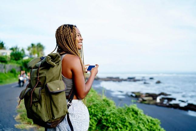 Cheerful dark skinned female traveller holding smartphone device in hands while trekking around nature environment, happy smiling woman with backpack enjoying new adventure during holiday time