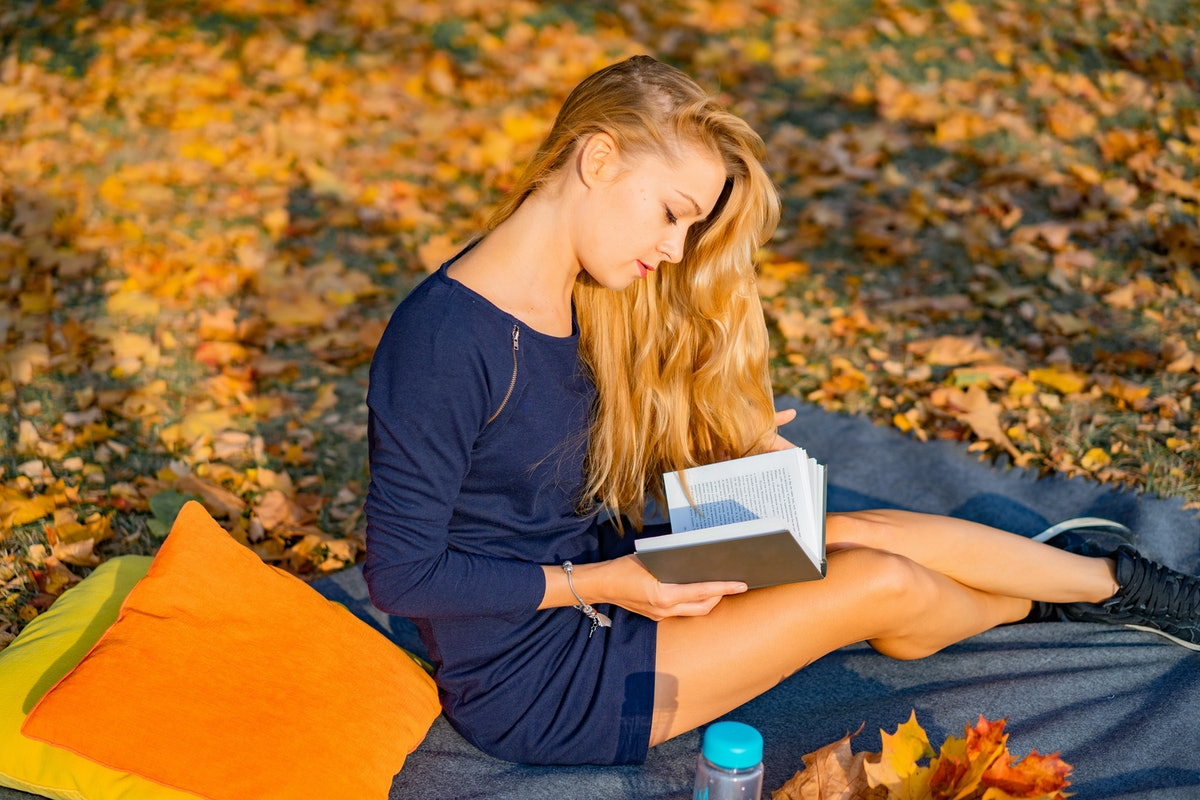 young female in the autumn park. A woman in an autumn park is reading a book, lying on a plaid, autu...