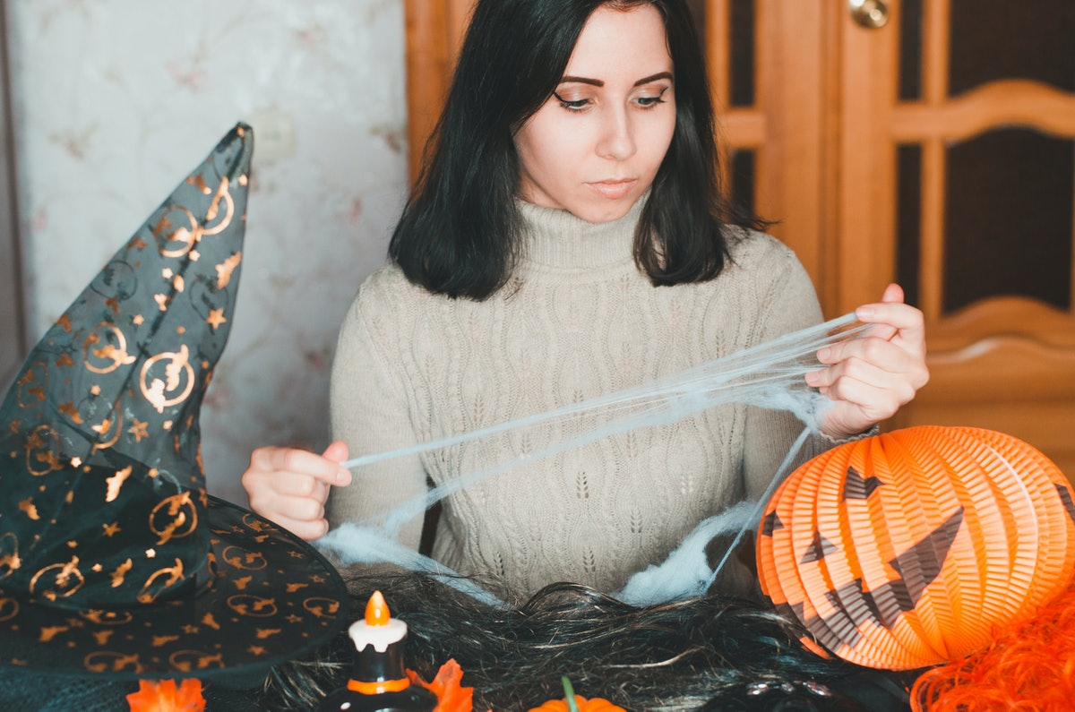 Young woman getting ready for halloween and keeps fake spiderweb among holiday decorations and elements for costumes. Portrait indoors