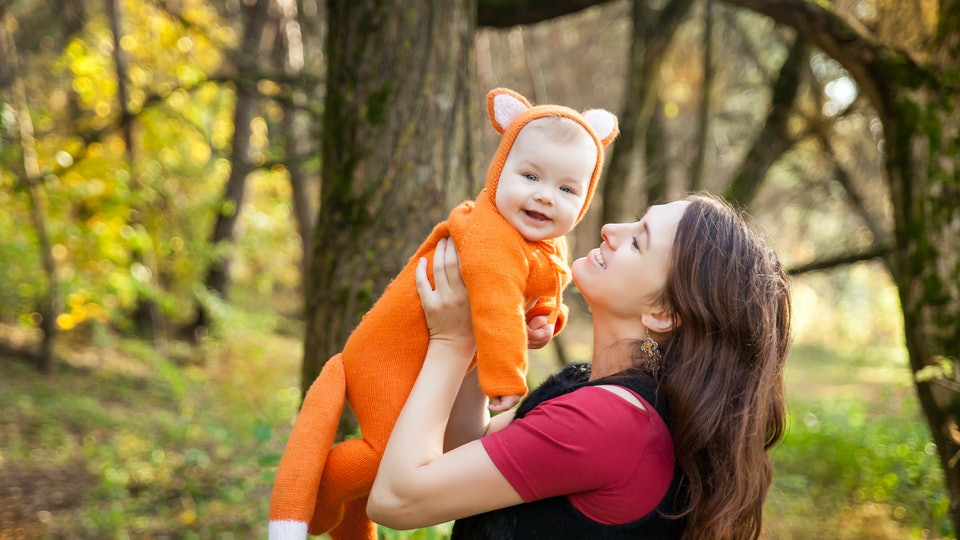 Happy mother with her baby girl dressed in fox costume in autumn forest. Fall halloween session