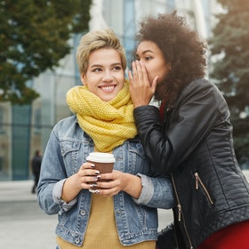 Two female friends gossiping outdoors. Girls walking around autumn city, drinking coffee and sharing secrets. Leisure, friendship and privacy concept
