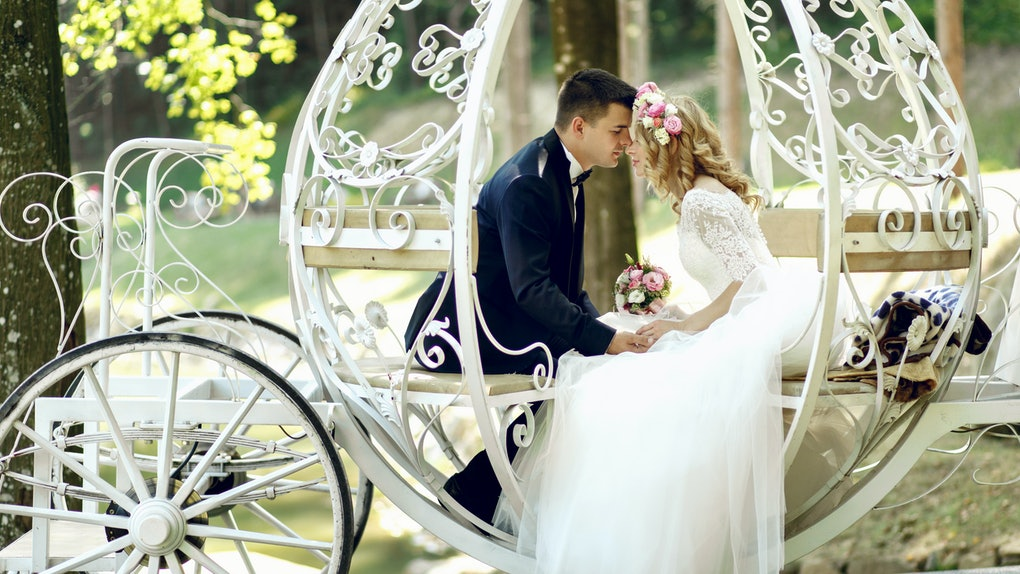 Handsome groom kissing blonde beautiful bride in magical fairy tale carriage in sunlit park