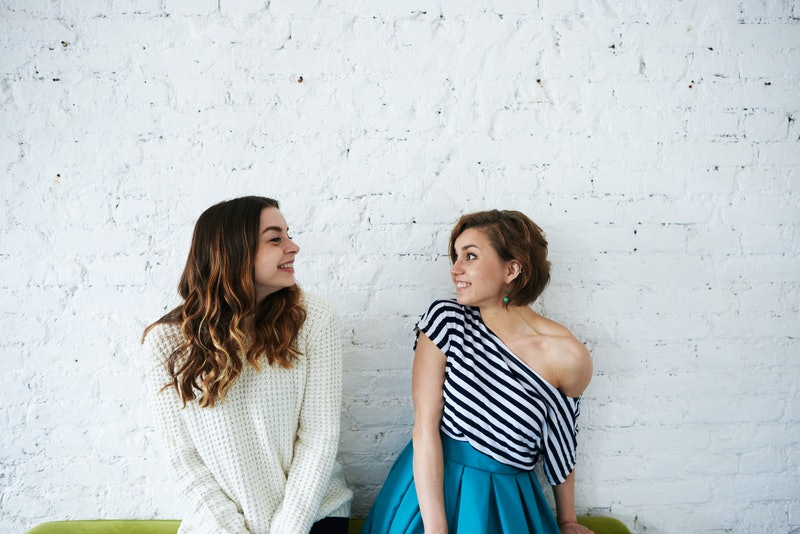 People, youth, happiness, joy and friendship. Two happy beautiful European young women friends or siblings wearing trendy clothes, posing at white brick wall, looking at each other and smiling