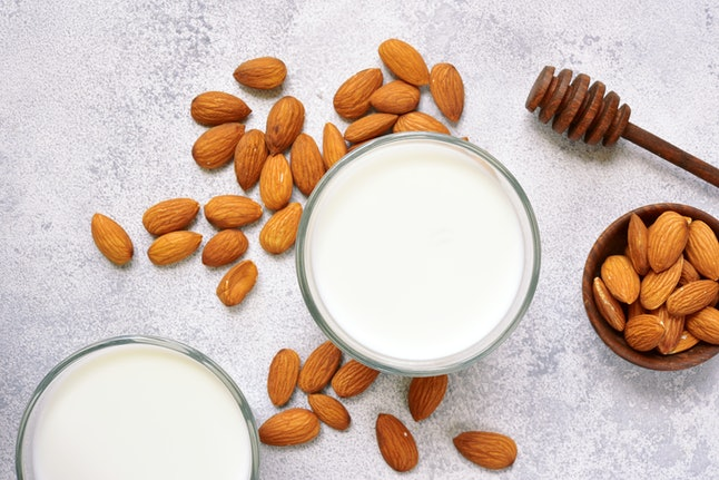 Homemade organic almond milk in a glass on a light slate, stone or concrete background.Top view with copy space.