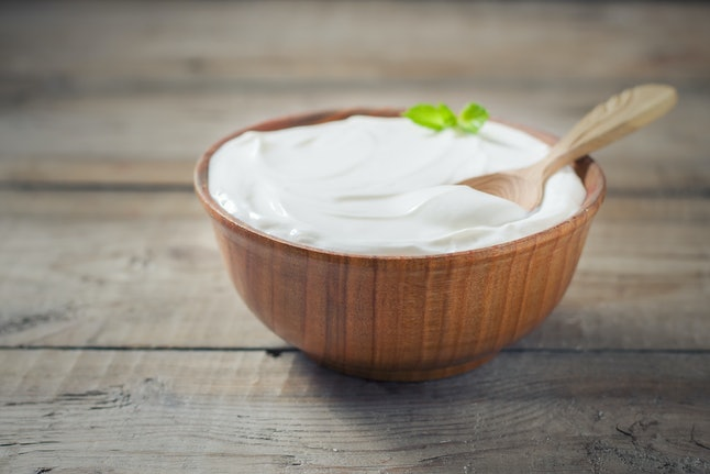 Greek yogurt in a wooden bowl on a rustic wooden table. Selective focus