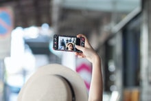 A woman wearing a hat is taking a selfie using her cell phone. Women taking a selfie on the footpath...