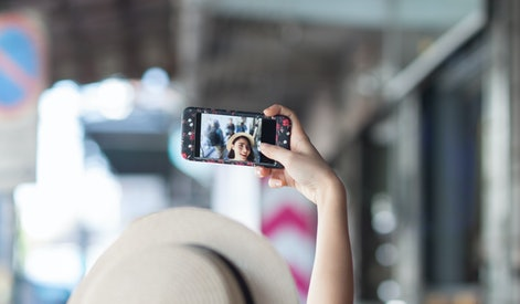 A woman wearing a hat is taking a selfie using her cell phone. Women taking a selfie on the footpath while in the airport.