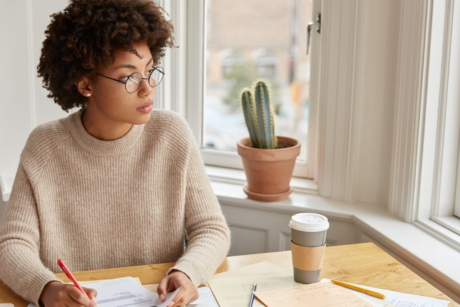 Study education, work concept. Thoughtful female banker fills in documentation, makes accountings, holds pen, dressed in casual oversized sweater, poses in coworking space with coffee and papers