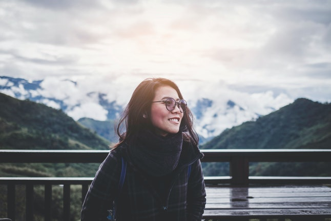 Portrait of smiling Asian woman wearing sunglasses with foggy forest view and breathtaking mountain scenery in background during winter season in Taiwan suburb, solo traveler and backpacker concept.