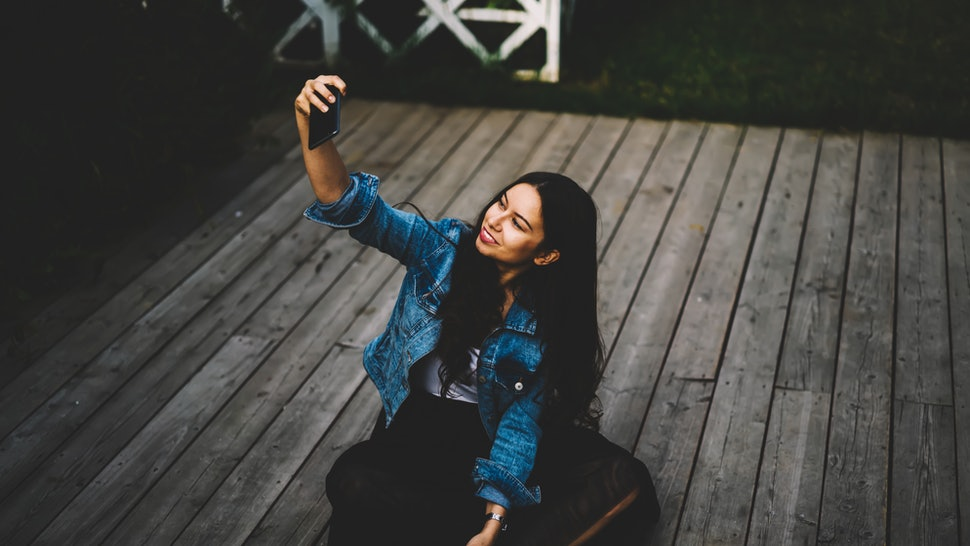 Stylish hipster girl with gorgeous long brunette hair making selfie photos on modern cellular sitting on wooden floor outdoors.Cheerful young woman with mobile phone in hand taking pictures for blog
