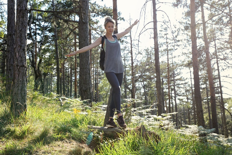 Woman balancing on fallen tree. Freedom ,fun , sport activities in nature
