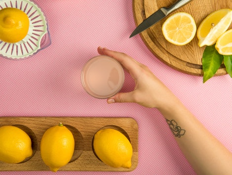 top view of female hand with glass of lemon juice on pink table with squeezer and lemons on wooden boards