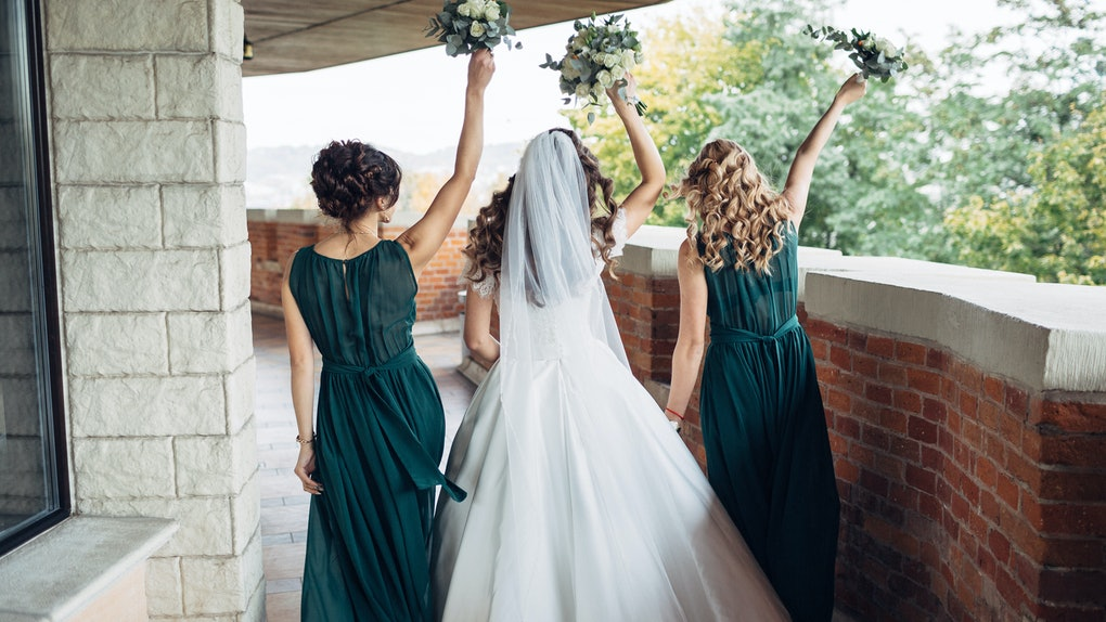 Look from behind at bride and bridesmaids in green dresses dancing on the balcony