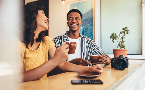 Friends talking and smiling while having coffee tighter at coffee shop. Man and woman having coffee together with a digital camera on table.