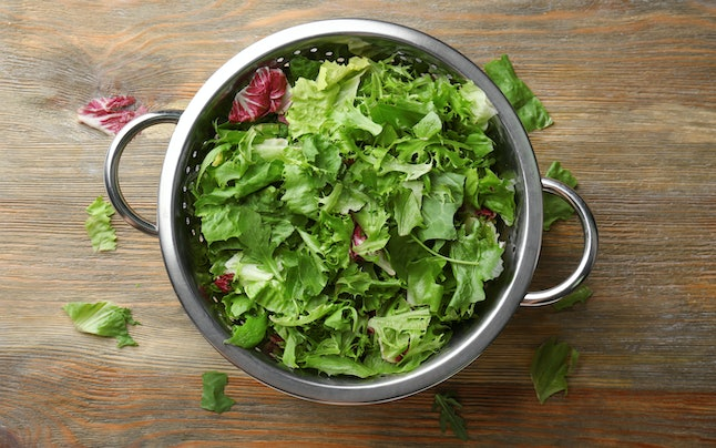 Colander with mixed salad leaves on wooden table