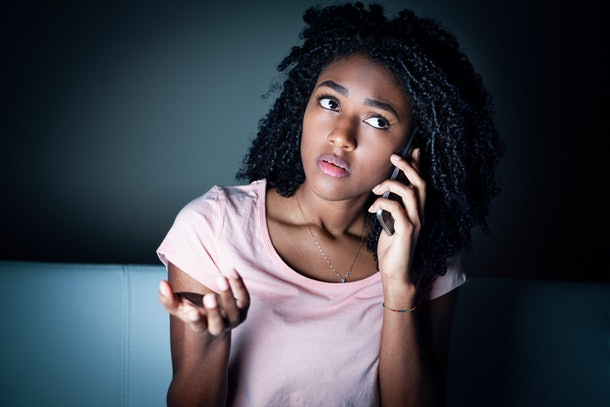 Black woman using cellphone at night