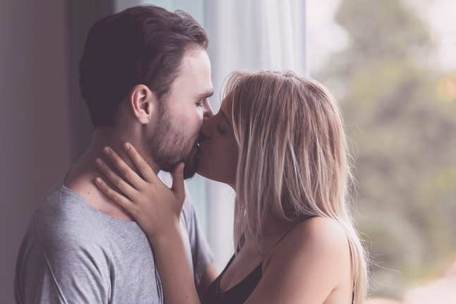 Couple hugging together. White youngman and woman standing near window with autum leafs in background. Passionate kiss to each other.