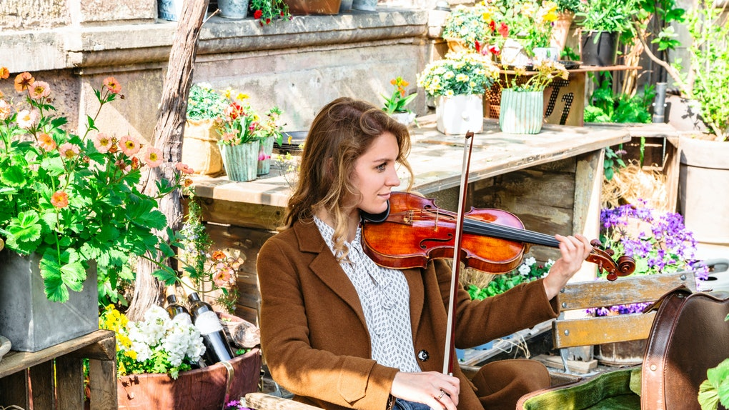 Young woman sits in autumn garden playing violin