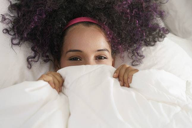 Portrait of happy black girl looking at camera undercover. Young African American woman waking up at home, smiling while lying in bed.