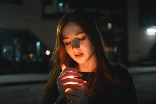 Young redhead woman with a burning lighter in the night city.