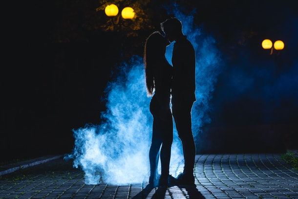 The man and woman kissing on the street on a blue smoke background. night time