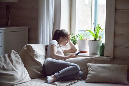 Woman upset after reading bad message on phone at home. Frustrated sad female crying, suffering, not in mood, thinking, depressed, stressed sitting on comfortable sofa near window holding smartphone