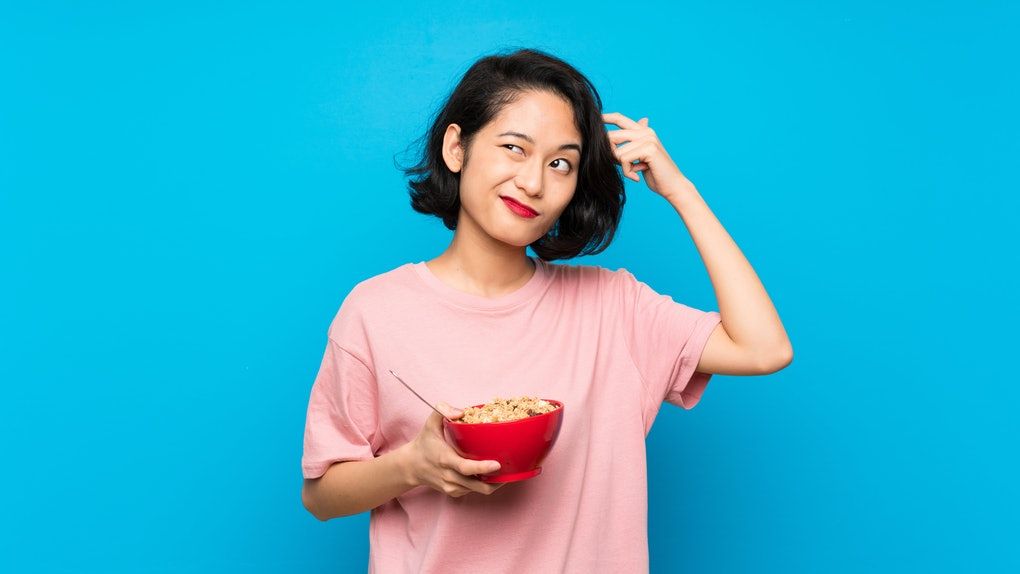 Asian young woman holding a bowl of cereals having doubts and with confuse face expression