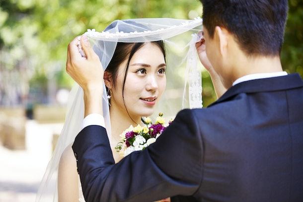 asian groom lifting up bridal veil to kiss beautiful bride.