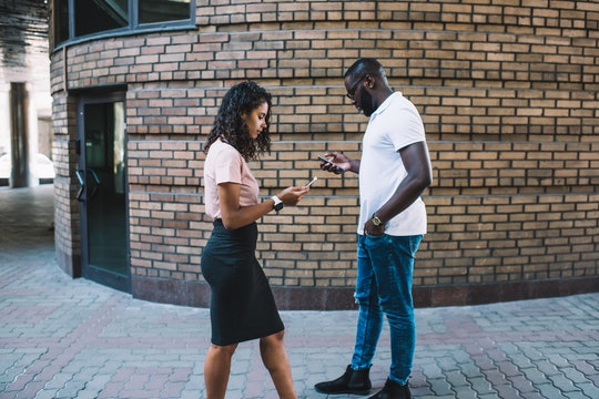Young woman and man walking with smartphones outdoors ignore real communication prefere online chatting, African American hipsters using cellphone gadgets having addiction to modern technologies