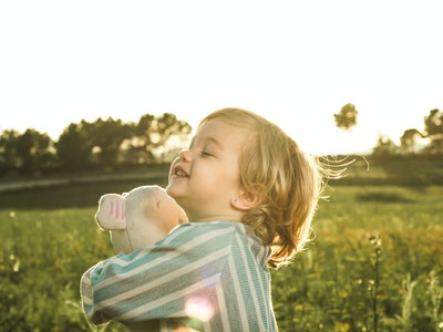 Happy little girl playing with a stuffed animal on the field. Kid hugging a teddy bear.