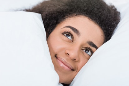 close up view of young african american woman laying in bed