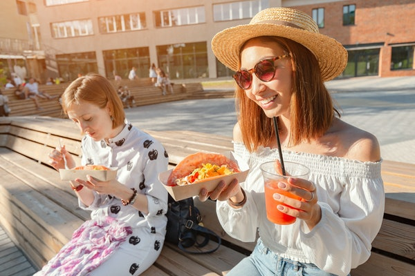 Two girls eat traditional Mexican fast food tacos and drink michelada on the street. Communication and takeaway food concept