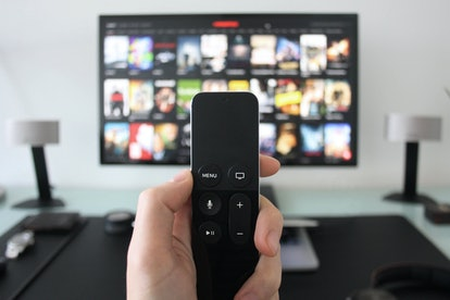 Hand holding a TV remote while watching shows on a streaming service on Television.