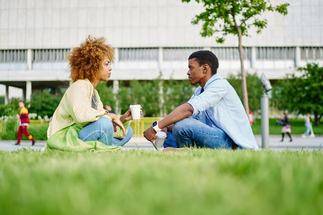 African american hipster girl sitting with boyfriend and communicating about relationship.Two friends talking with each other and drinking tasty coffee sitting on green grass in park