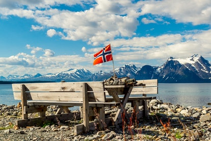 Picnic site rest stop area wooden table decoration and norwegian flag on lake fjord shore. Holidays relaxation on trip. Scandinavia Europe.