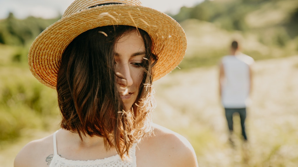Frustrated young woman looking in distance, think about relationships, staying separately with man, stubborn boyfriend on background looking at sad upset girlfriend, not talking after quarrel close up
