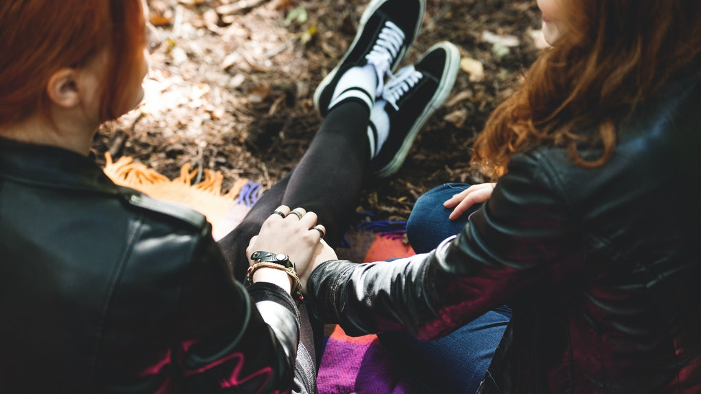 High angle of lesbian girls holding hands, sitting on a blanket in the park