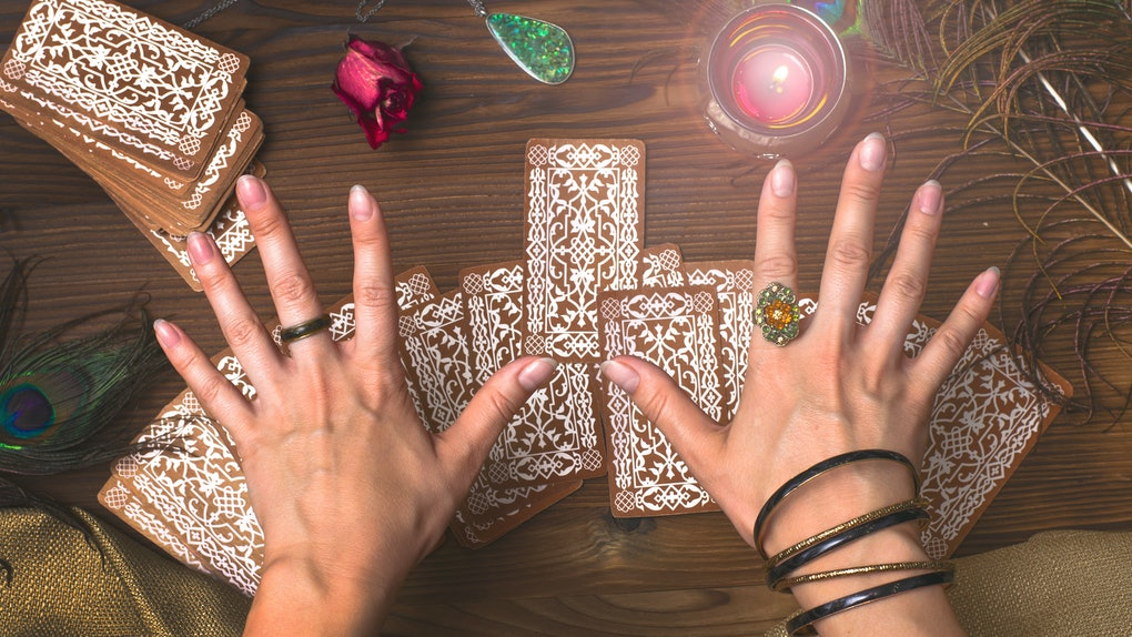 Fortune teller female hands and tarot cards on wooden table. Fortune teller.