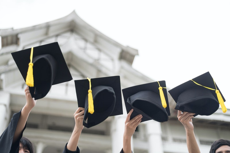 Graduation day. Many hand holding Row of graduation hats on Sky background. Happiness feeling, Commencement day, Congratulation. Education Concept. Setup studio shooting.