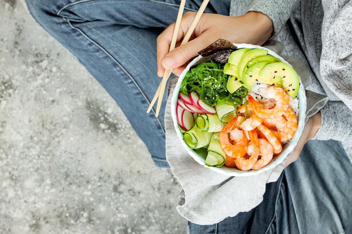 Girl in jeans holding shrimp poke bowl with seaweed, avocado, cucumber, radish, sesame seeds.