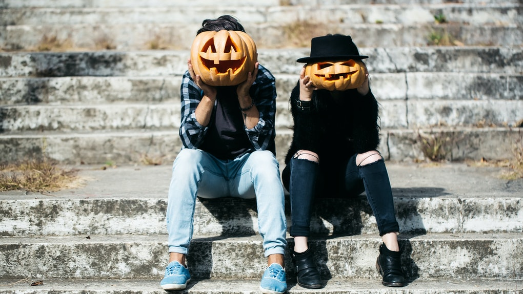 young halloween couple of man and girl or woman in black witch hat in jeans sitting on stony stairs with traditional autumn holiday symbol of orange spooky pumpkin outdoor
