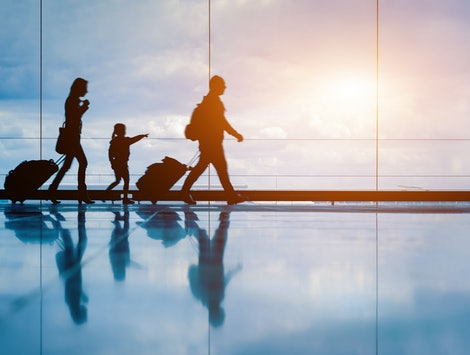 Family at airport travelling with young child and luggage walking to departure gate, girl pointing at airplanes through window, silhouette of people, abstract international air travel concept