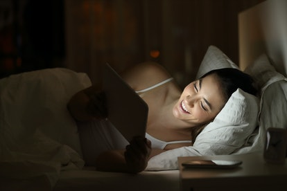 Happy woman watching tv or media content in a tablet on the bed in the night