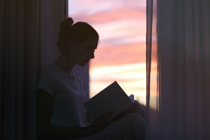 Silhouette of young woman reading book on windowsill at home