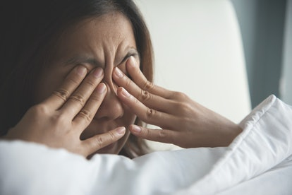 Person rubbing eyes with her hands on her bed. Getting cum in your eye is very painful.