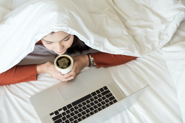 Charming young woman covering head with white blanket lying on bed and watching tv or movies streaming on laptop and holding a cub of hot coffee in winter season.