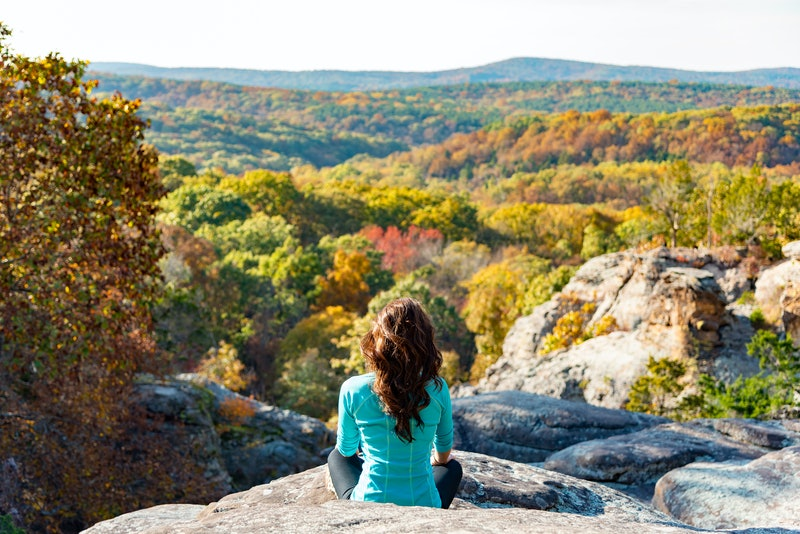 Woman meditating on cliff overlooking fall forest