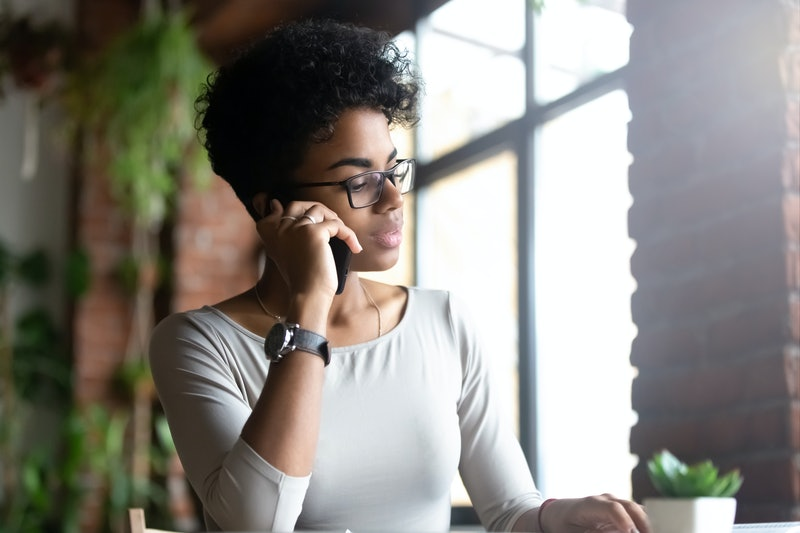 Focused african American millennial woman in glasses talk on cellphone working consulting client, concentrated pensive biracial female in spectacles speak chat on smartphone distracted from studying